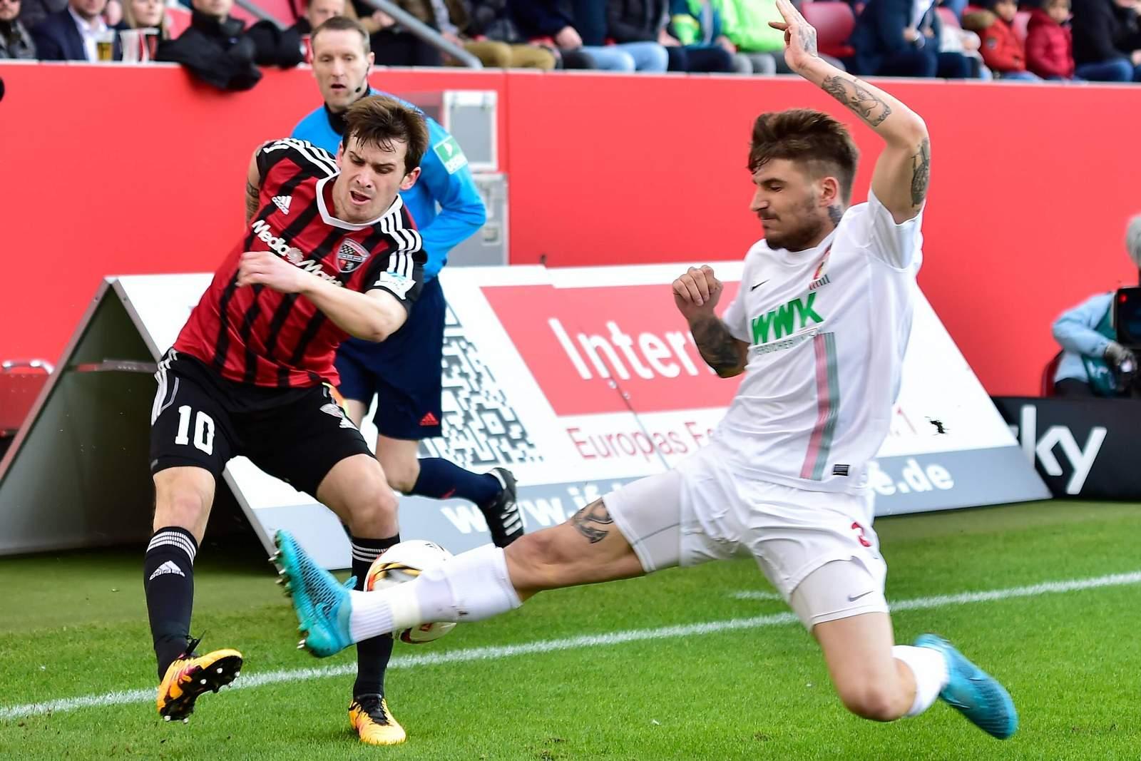 Konstantinos Stafylidis will die Flanke von Pascal Groß verhindern. Jetzt auf Ingolstadt gegen Augsburg wetten!