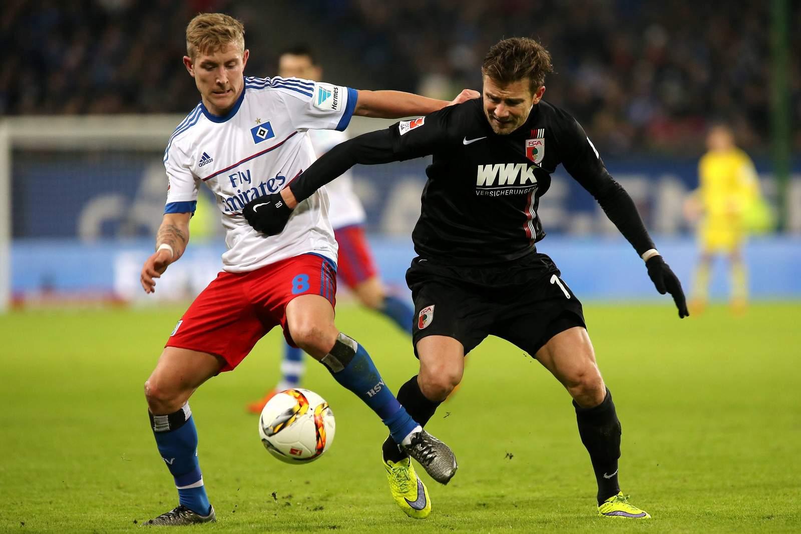 Lewis Holtby im Zweikampf mit Daniel Baier. Jetzt auf HSV gegen Augsburg wetten!