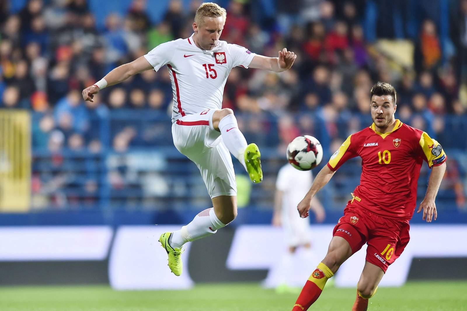 Kamil Glik im Duell mit Stefan Mugosa. Jetzt auf die Partie Polen gegen Montenegro wetten