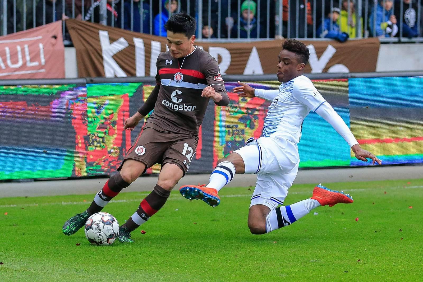 Ryo Miyaichi vom FC St. Pauli gegen Anderson Lucoqui von Arminia Bielefeld